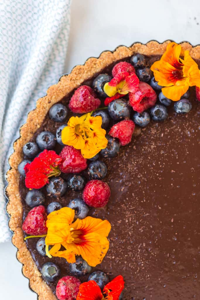 Close up of chocolate tart with flowers and berries