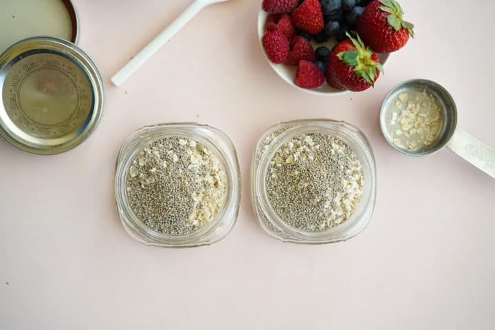 Two mason jars with oats and chia seeds, bowl of fruit