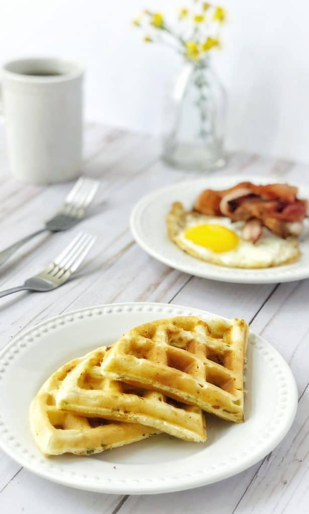 plate of waffles with eggs and bacon