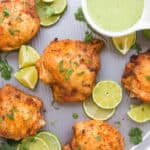 Close of up of roasted chicken thighs with lime around and green sauce