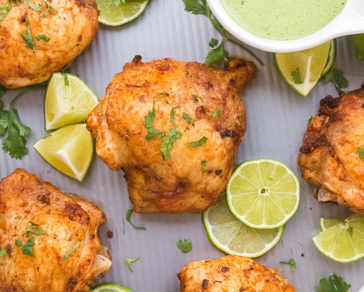 Close up of roasted chicken thai with lime as garnish and green sauce on the side