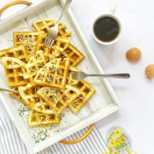Tray of waffles, coffee and some flowers