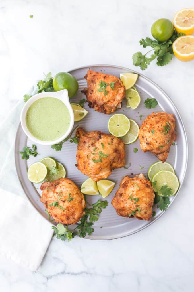 Plate full of chicken thighs with lime slices and green sauce in a bowl