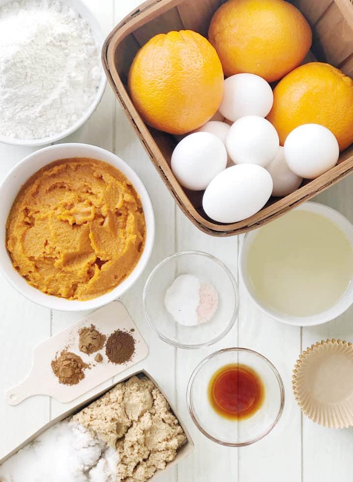 Bowls of ingredients of pumpkin, eggs, orange, spices, flour