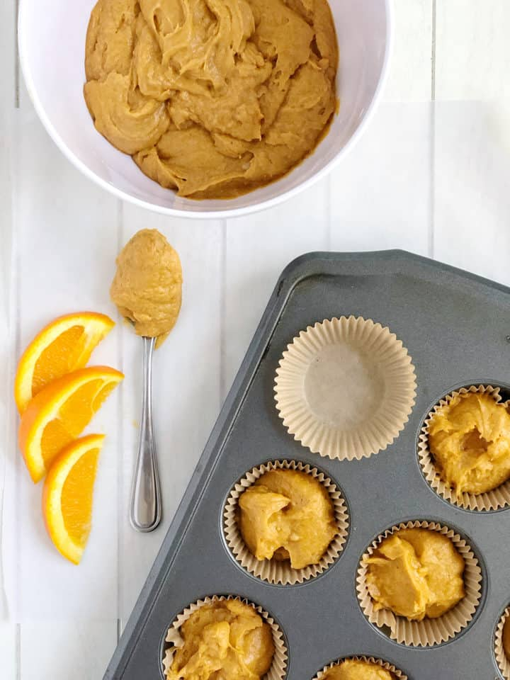 Muffin tin with pumpkin batter in bowl with orange slices as garnish