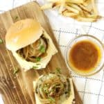 homemade veggie burger on a wooden board next to fries and dipping sauce