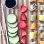 Cut cucumbers, strawberries, cut sushi and soy sauce, chopsticks