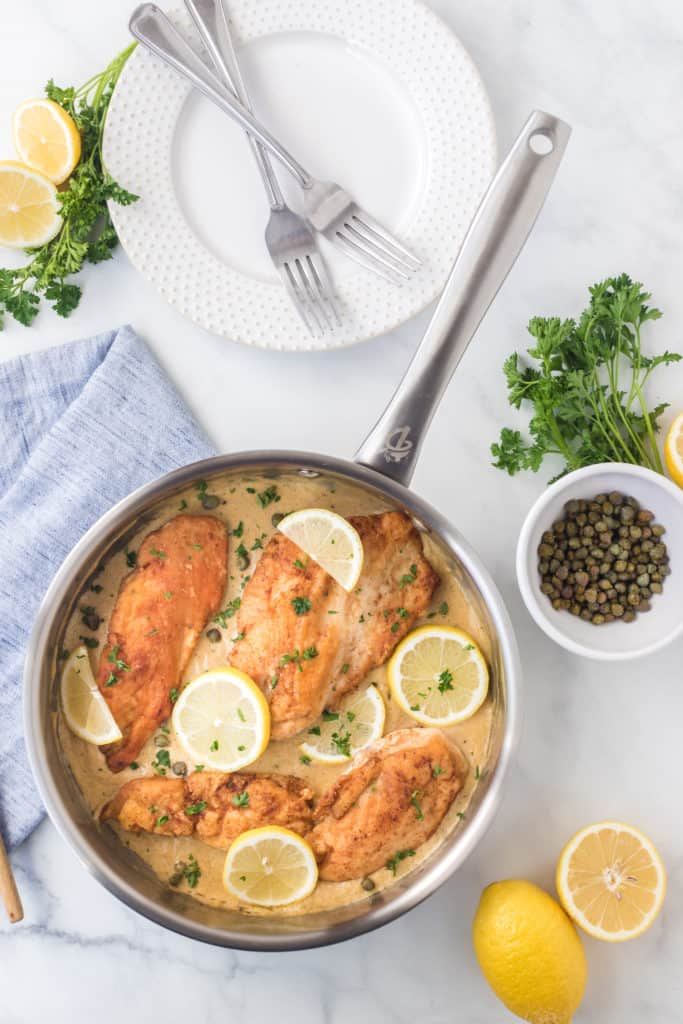 Pan of cream of lemon picaata chicken with capers on the side