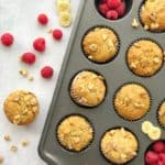 Banana Muffins in muffin in with some raspberries as side dishes