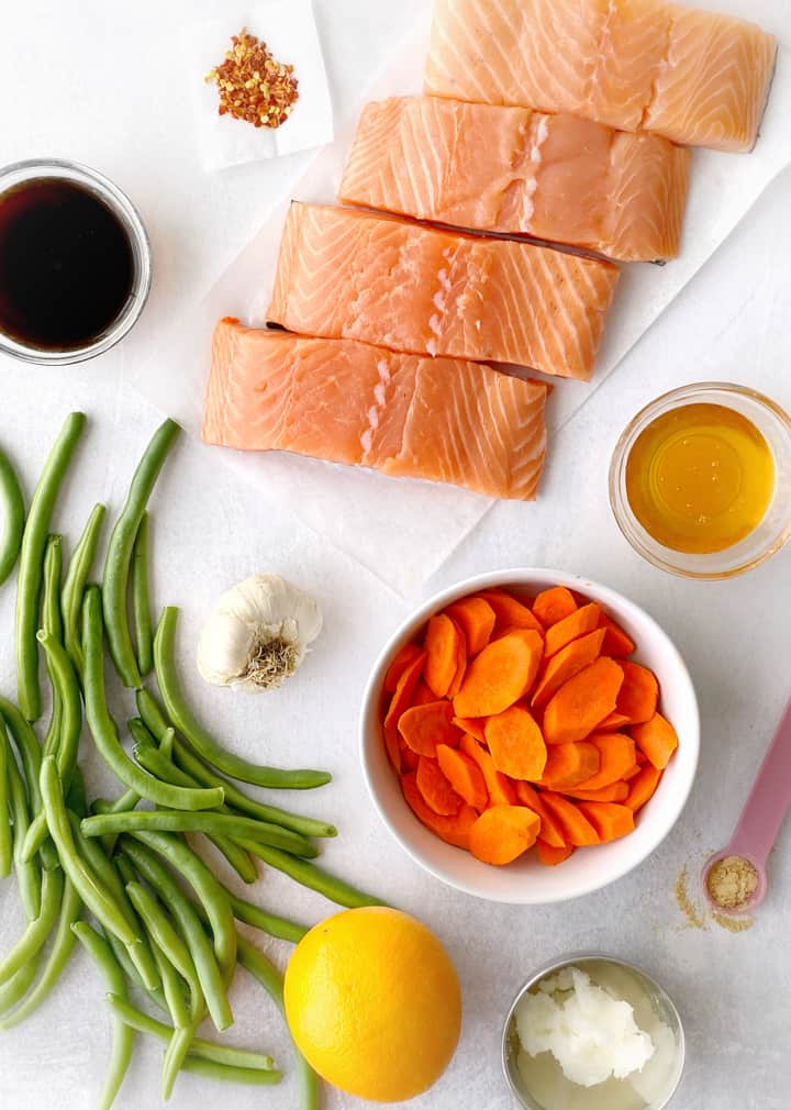 Flat lay photo of ingredients including salmon filets, green beans, carrots