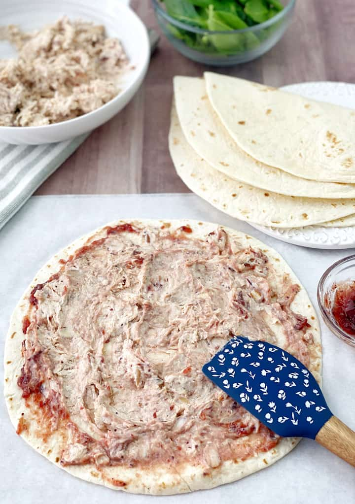 Tortilla with cream cheese mixture on top of tortilla