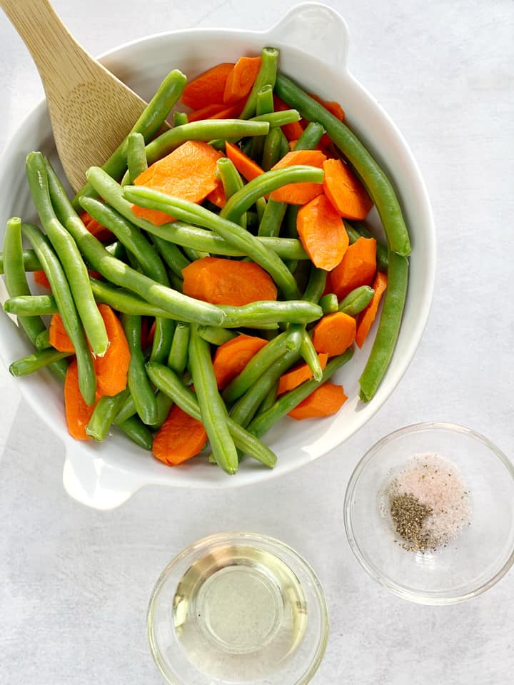 Bowl of green beans and carrots with oil next to it and seasonings
