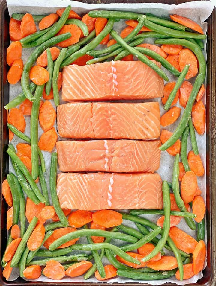 Baking sheet with raw vegetables and salmon