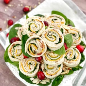 Stack of cranberry turkey pinwheels on a plate with cranberries around.