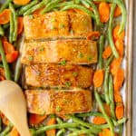 sheet pan of 4 salmon filets with green beans and carrots around