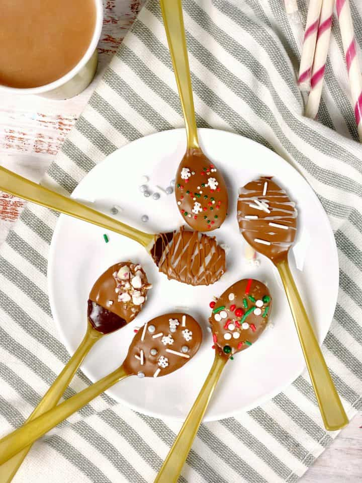 chocolate spoons on a plate with hot cocoa next to it on a striped napkin