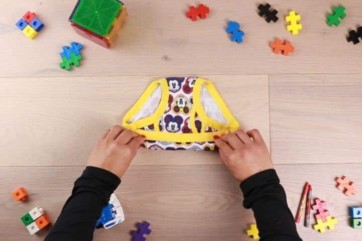 hands with black sleeves folding underwear surrounded by toy decor