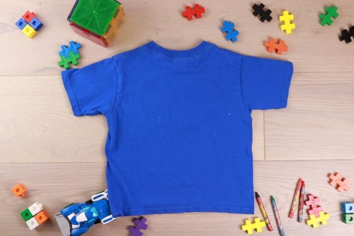 Blue shirt laid flat with toys around as decor