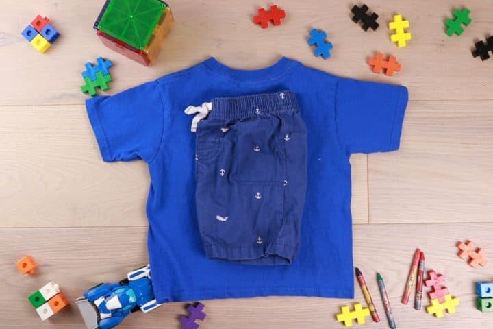 Blue shirt and then shorts folded on top surrounded by toys as decor