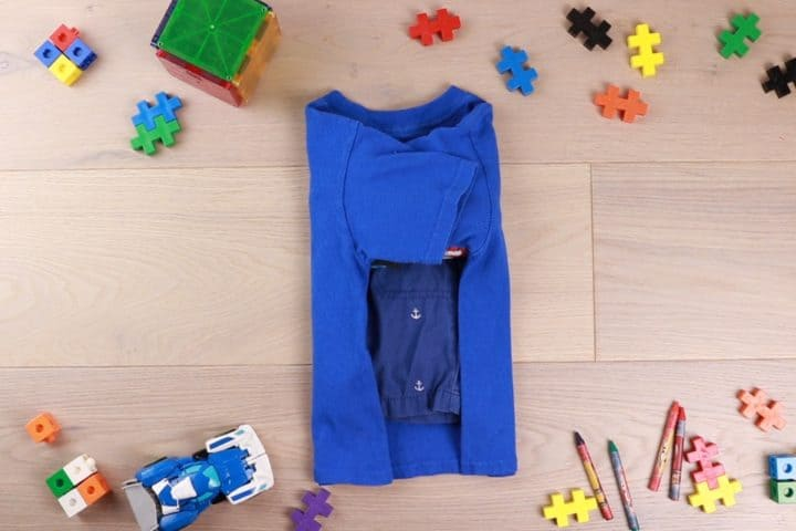 Folded tshirt surrounded by toys