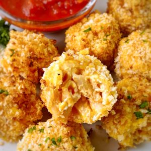close up of mac and cheese balls with marinara on the side