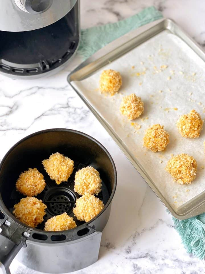 mac and cheese in air fryer next to baking sheet with prepared mac and cheese balls