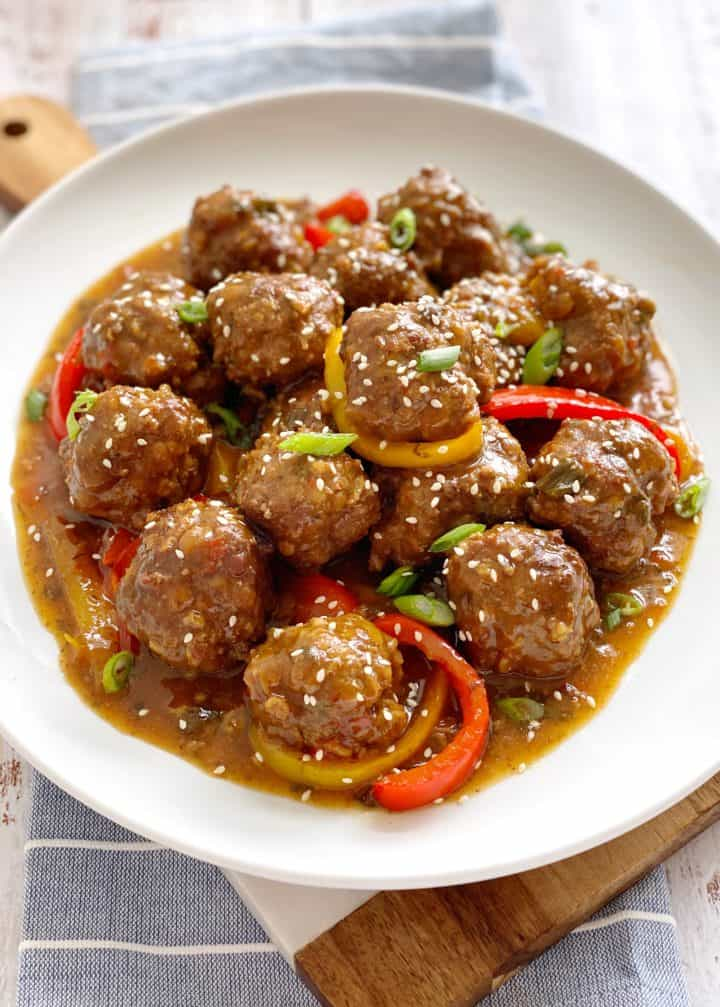 sweet and sour meatballs on a plate with bell pepper and garnish