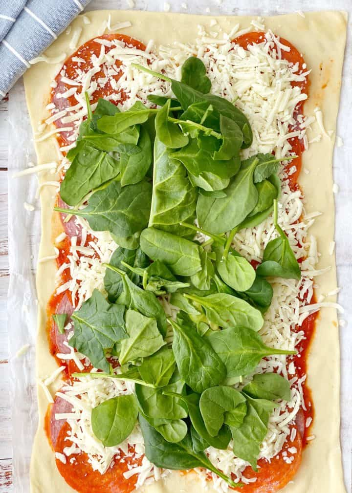 pizza dough with pizza sauce cheese and spinach