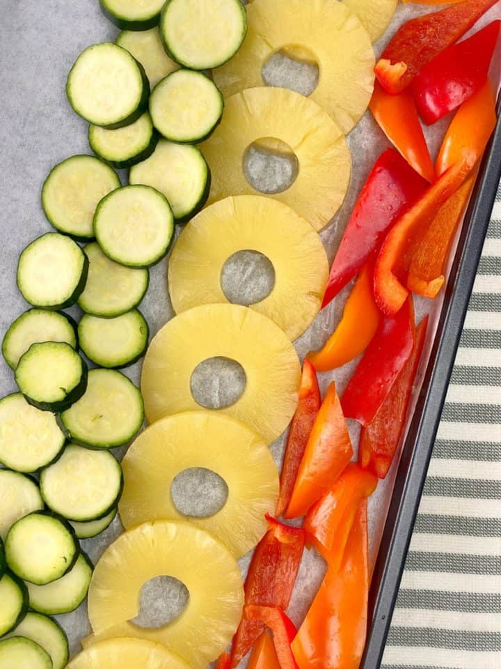 baking sheet with zucchini, pineapple, and bell peppers