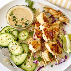 Chicken satay on a plate with cucumbers