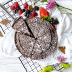chocolate cake on a plate with berries and flowers around it
