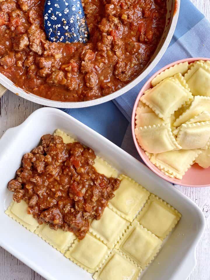 Meat sauce on top of ravioli