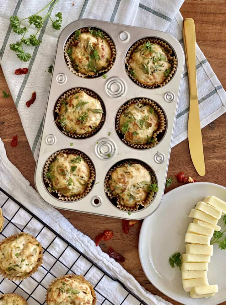 muffin tin with muffins next to slices of butter