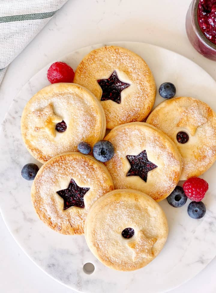 berry pies with stars in the middle and berries around it