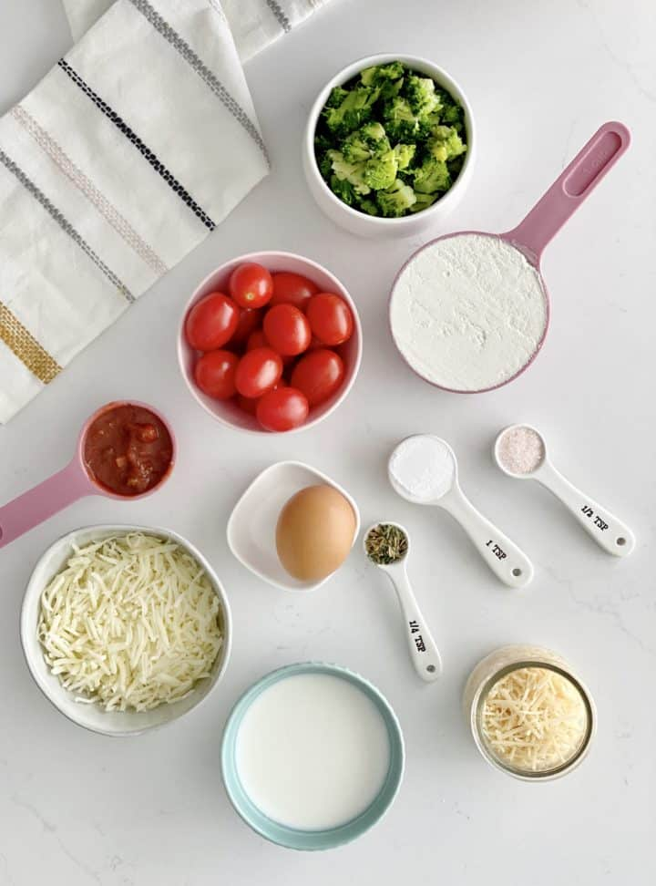 flat lay photo of ingredients including cheese, tomatoes, seasonings, and cheese