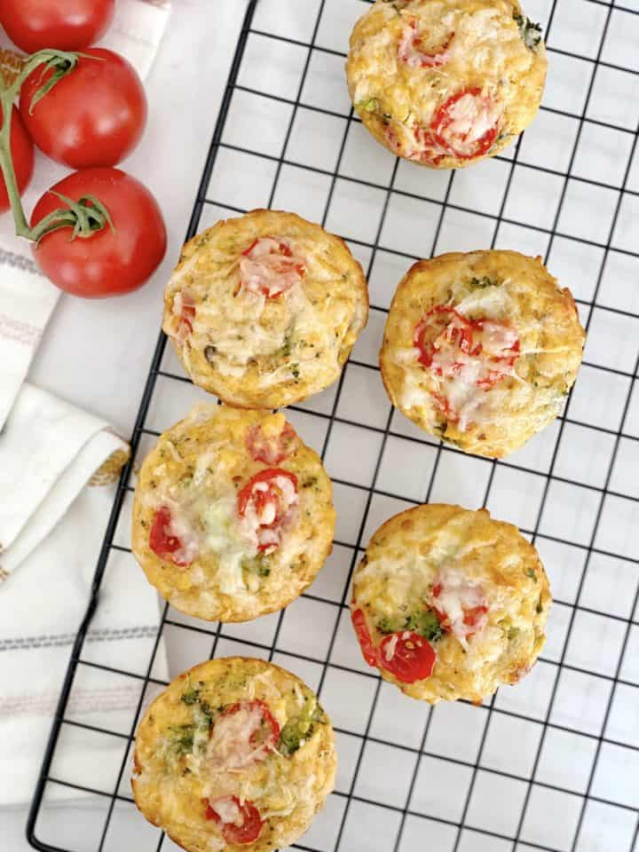 muffins on a baking tray with tomatoes in photo