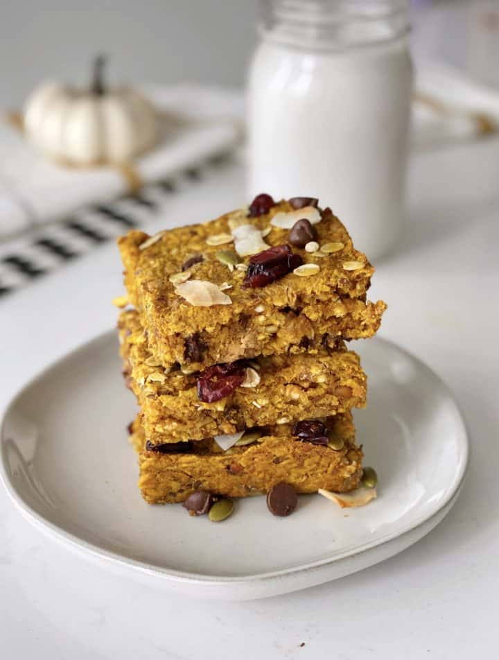 Pumpkin oatmeal bars stacked on a plate with milk behind it