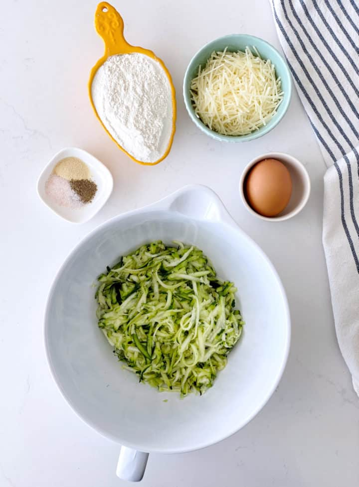 flat lay photograph of shredded zucchini, flour, egg and cheese