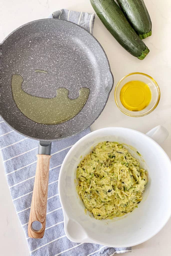 pan with oil next to egg and zucchini