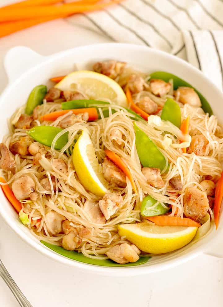 plate of filipino noodles with snow peas, chicken, lemon slices, sliced carrots, sliced cabbage in a bowl
