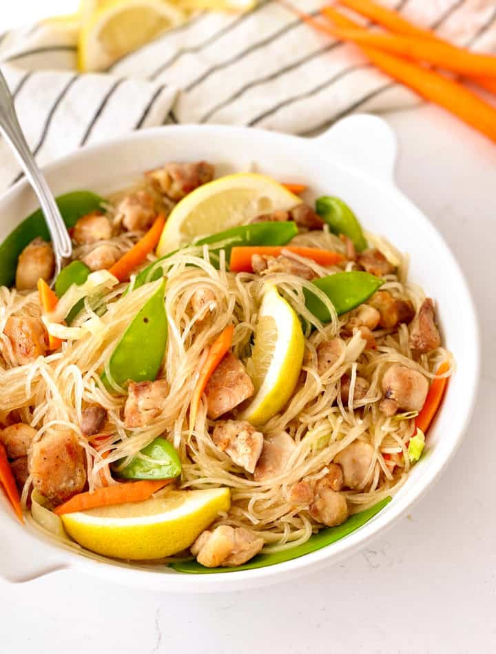 close up of pancit bihon with lemon and vegetables, chicken and fork