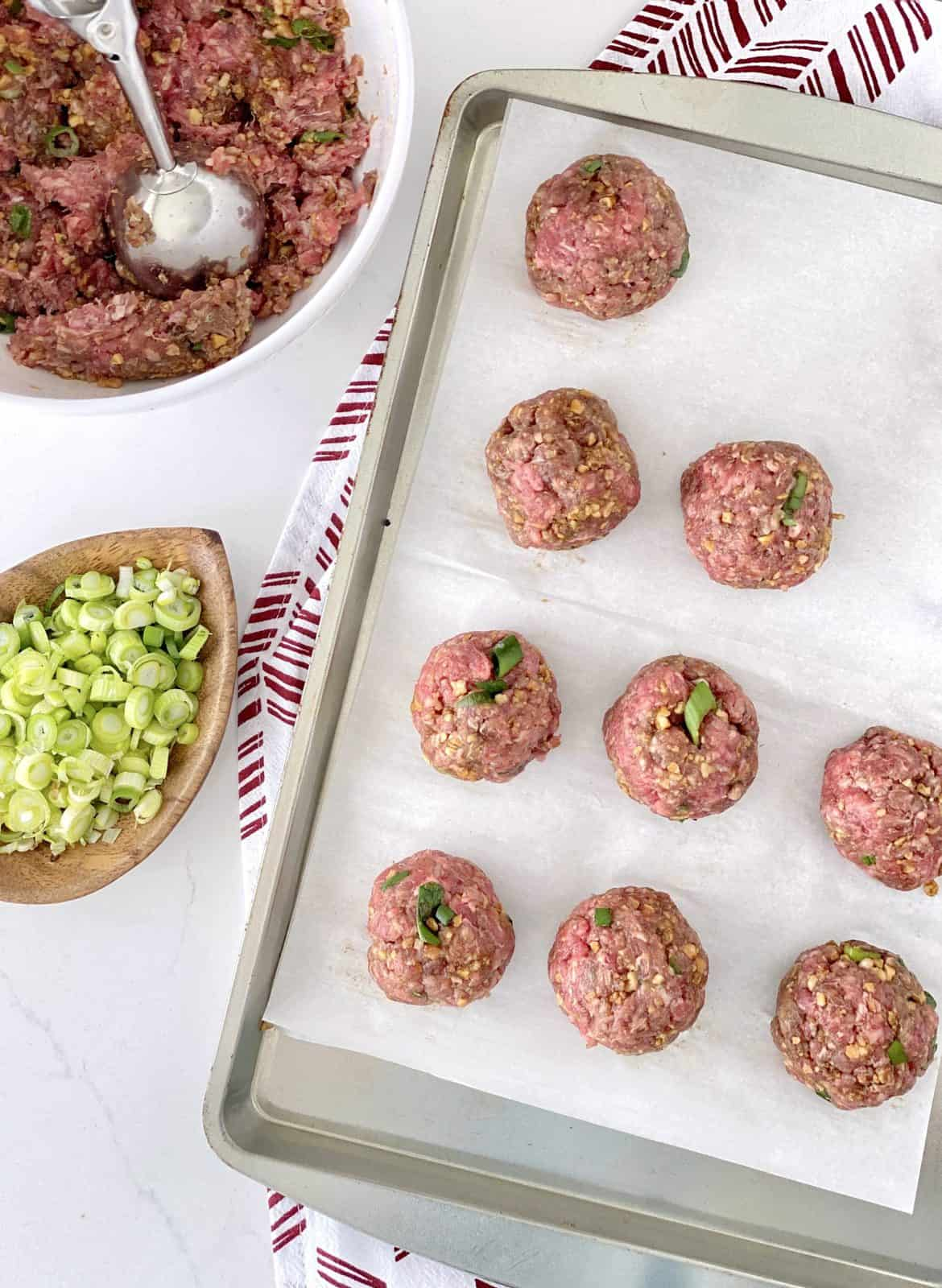 raw meatballs on parchment paper on top of a baking sheet