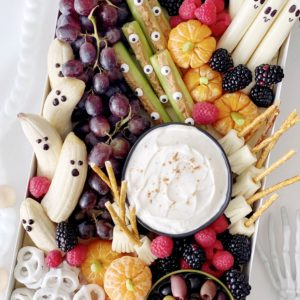Halloween Snack board with yogurt dip, grapes, banana ghosts, celery eyes, olives, pretzels and tangerine pumpkins