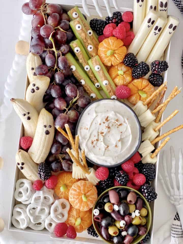halloween snack board with a variety of fruit and vegetables including grapes, string cheese brooms, yogurt, tangerine pumpkins