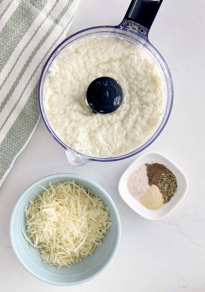 food processor with mashed cauliflower and parmesan cheese next to seasonings