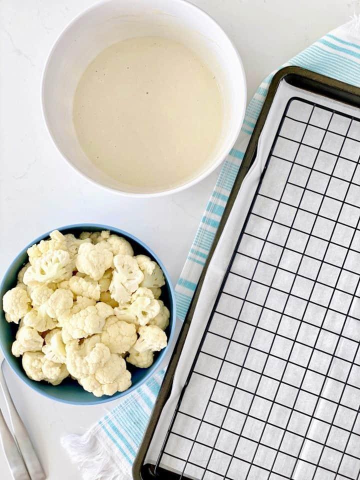 cauliflower and mixture next to baking sheet