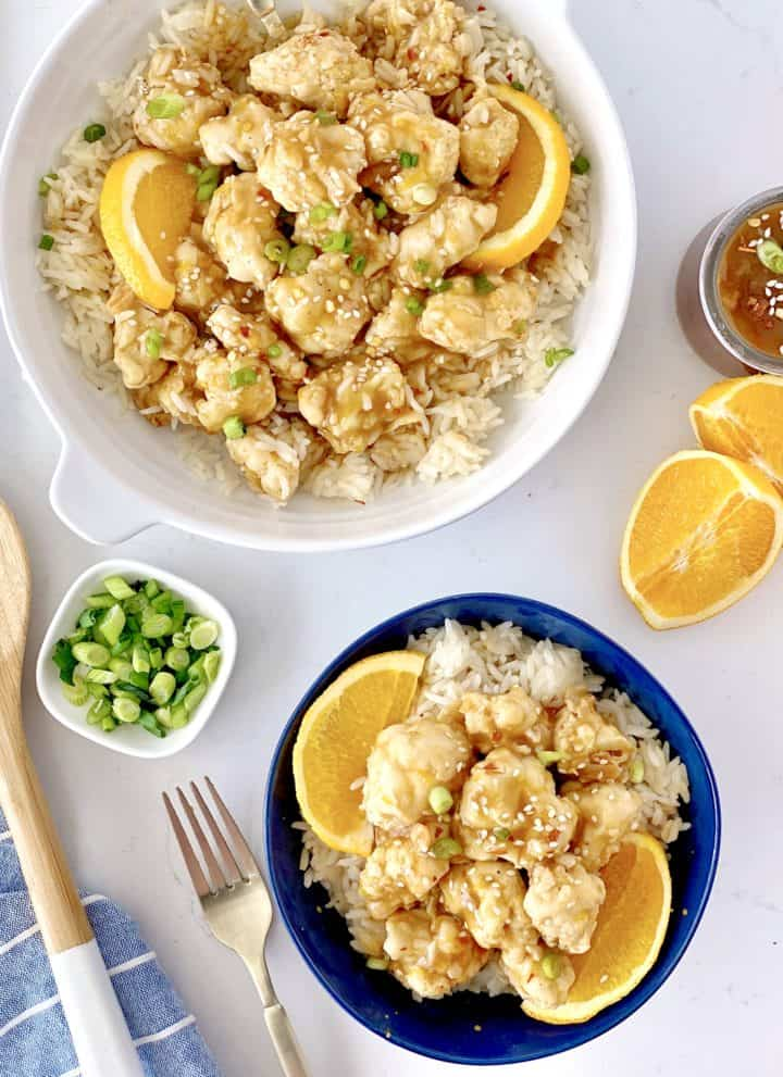 serving bowl of vegan orange chicken and a small indivdiual bowl