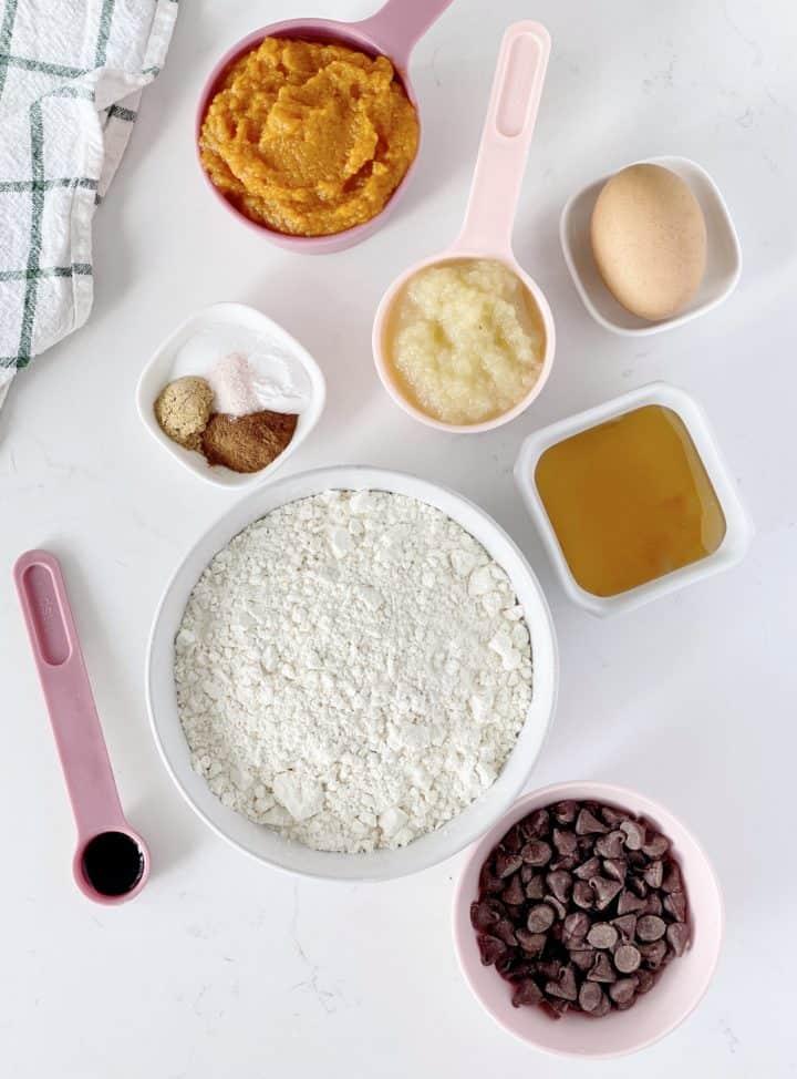 over the top shot of ingredients including flour, honey, applesauce, pumpkin