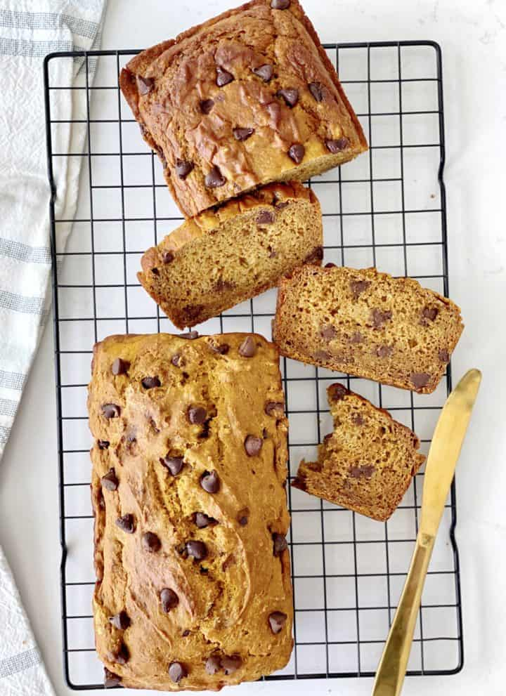 over the top shot of pumpkin bread cut with a gold knife on the side