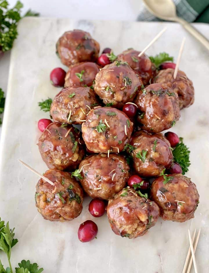 meatballs close up with cranberrys and garnish on a white plate